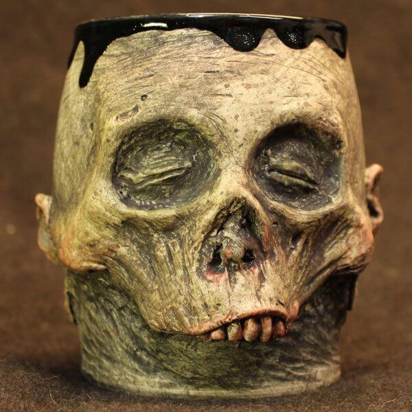 Handmade, detailed pottery zombie mug with dripping tar